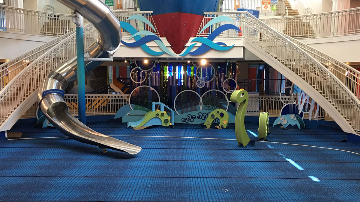 SafeLandings Installation at the Port Discovery Museum with custom printed carpet, large slide and dinosaur play equipment.