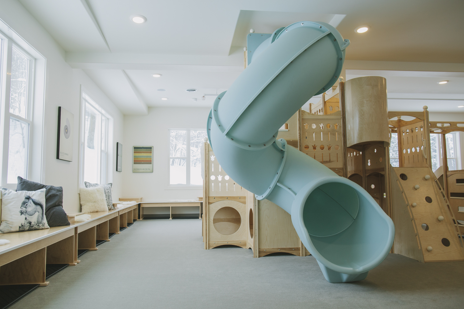 Safe Landings carpet system that is safe kids flooring and wood play ground with blue slide and rock wall.
