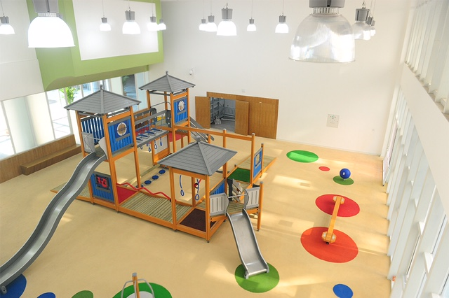 Long lasting indoor playground surfacing with custom cut sheet vinyl circles and an indoor playground with multiple slides. This installation meets ASTM F1292 standards.