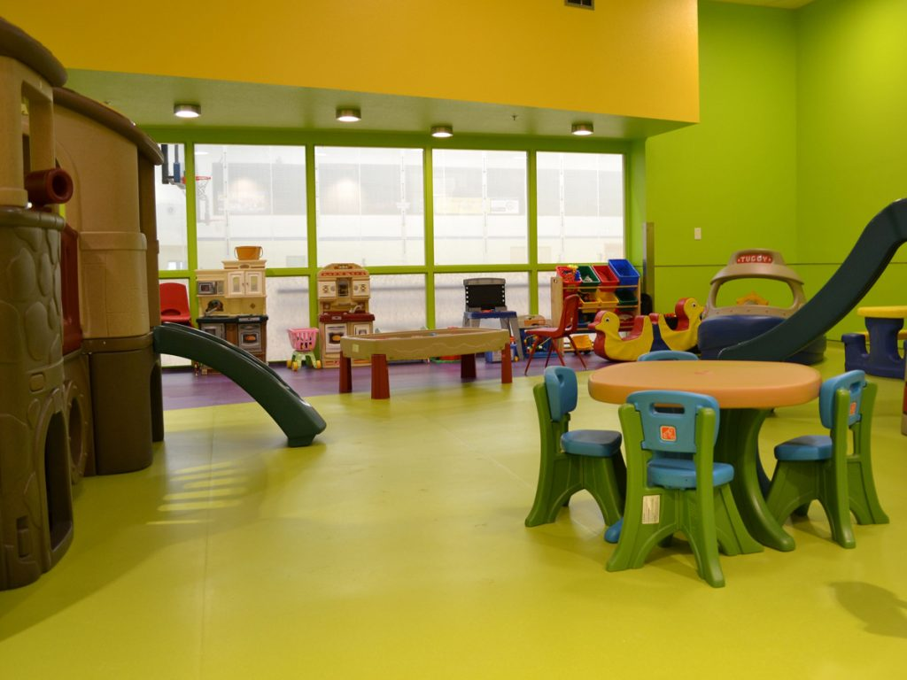 Green and purple sheet vinyl safety flooring for day cares with multiple play structure including two slides.