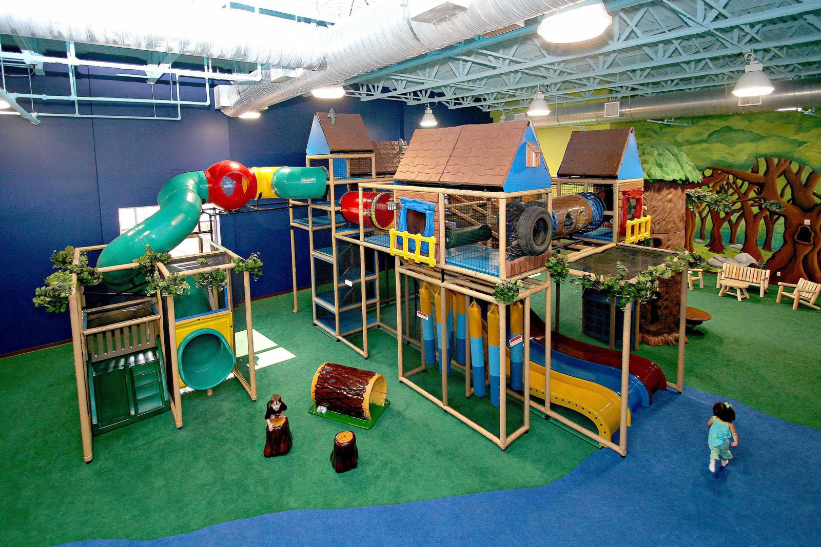 Two level indoor playground with multiple slides and a forest background with durable indoor playground carpeting that has cushioned floors.
