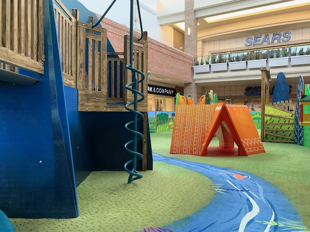 Custom designed carpeting with a river scene at an indoor mall play area. This play area has a few play structures and an orange tent.