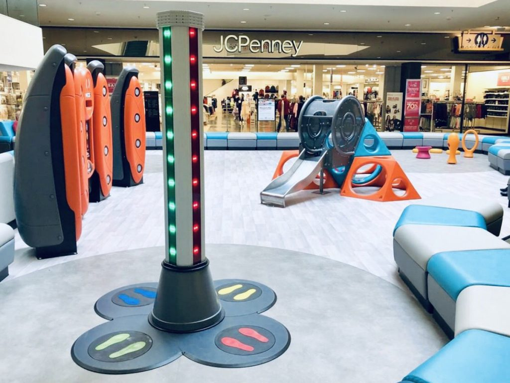 Two colored Safe Landings Resilient Sheet Vinyl System installed in shopping mall play area with multiple play structures.
