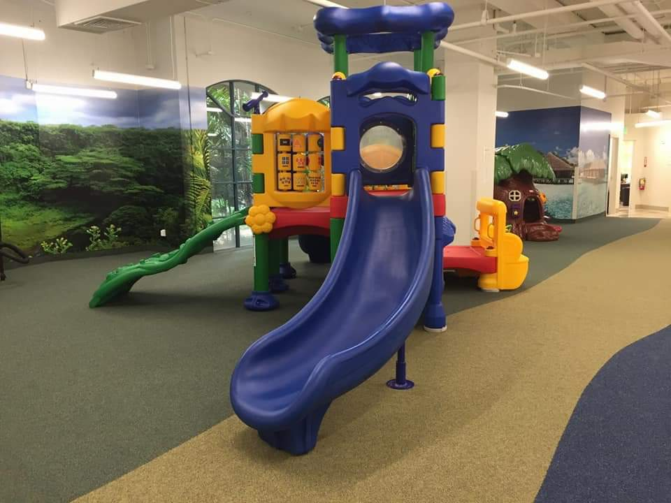 Indoor Play Ground Flooring With Custom Printed carpet, and a large plastic play fixture in middle of room with slide.