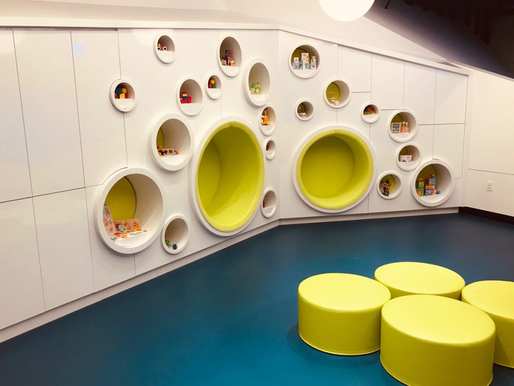 Blue sheet vinyl safe flooring with yellow circle stools and circle cubbyholes on the wall.