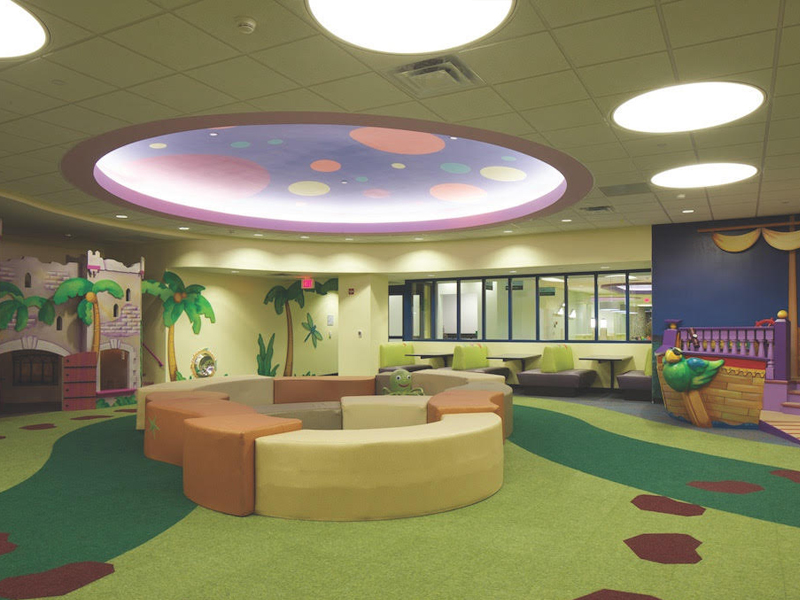 Compliant playground padding with a custom printed green carpeting with brown stepping stones inside a hospital indoor play center with a castle and ship play structure.
