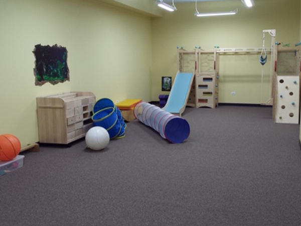 Safe flooring for kids at a community center playroom. There is a small wooden playground, and several tunnels for children to play in.