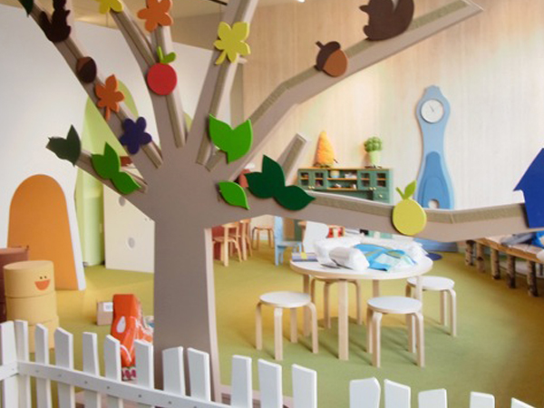Safe Flooring for Kids Daycare play area with white fence, tree, and multiple small tables for kids to play at.