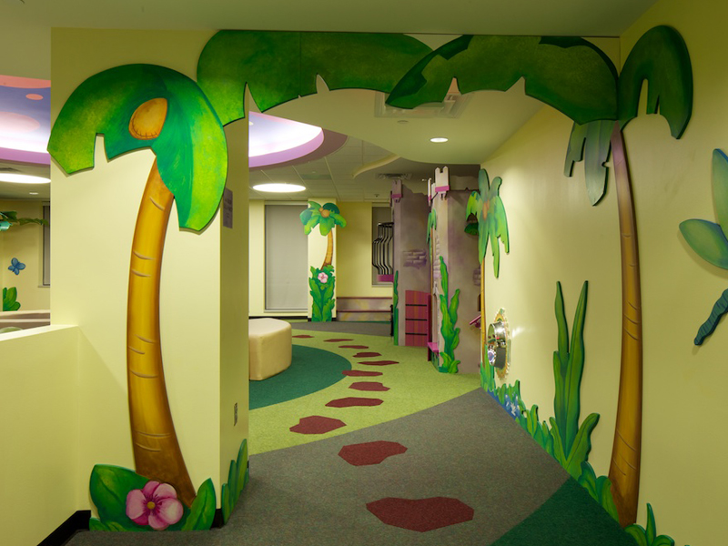 Custom jungle themed cushioned flooring for kids at a childrens hospital. The flooring is a custom print shock absorbing floor with stepping stones. There are jungle palm trees painted in the walls.