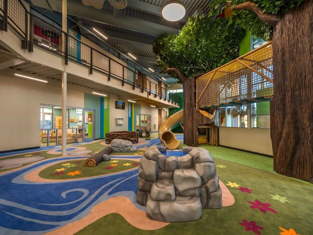 Carpet with custom print for an indoor religious play center that is compliant with playground fall height requirements. There are several play structures including a log, and a slide from the trees.