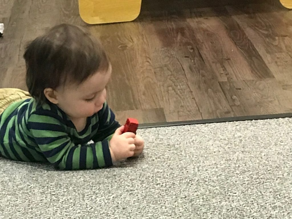 Toddler playing with red block on SafeLandings SafetyRug.