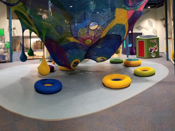 Safe kids flooring installed in a museum play room with unique knitted hanging balls.