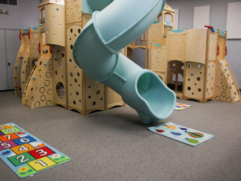 Indoor playground with a blue slide and long lasting impact absorbing carpeting.