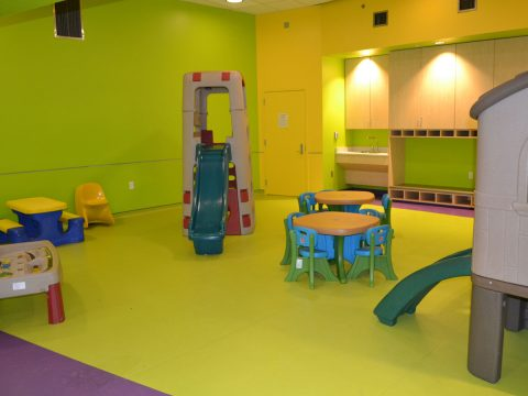 Bright green and purple SafeLandings Resilient Sheet Vinyl System at an indoor day care with small tables and several plastic play equipment.