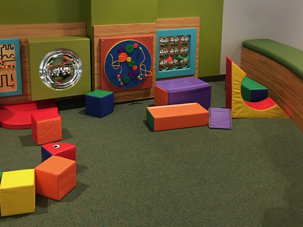 Image of day care flooring with shock absorbing carpeting, puzzel toys on walls and large foam block toys.