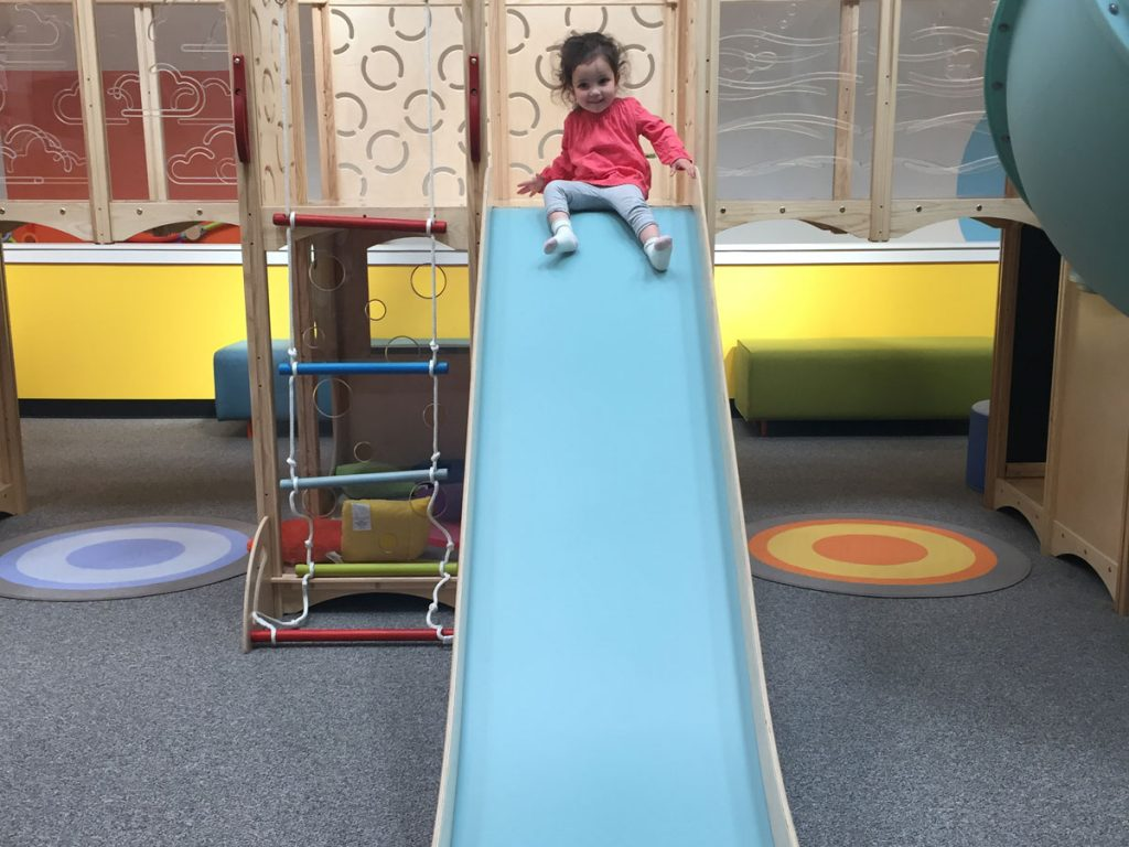 Child sliding down community play things play indoor playground with SafeLandings Shock Absorbing Carpet System.