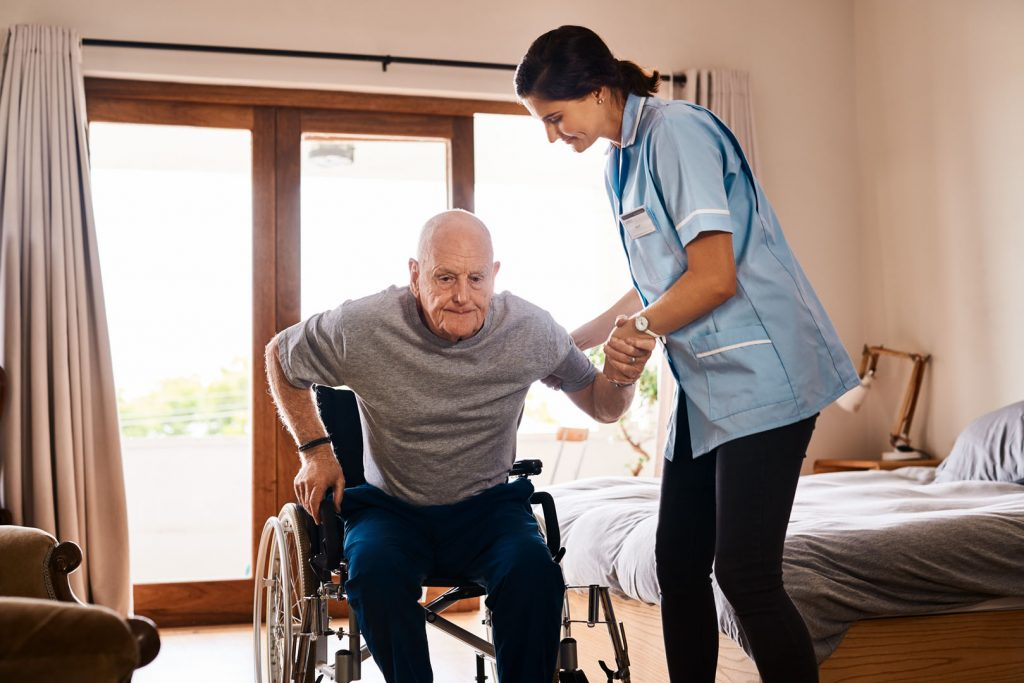 Elderly man in senior facility being helped out of a wheel chair by a nurse.