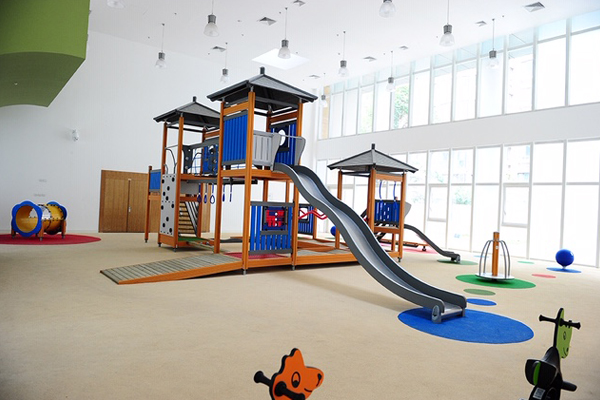 Indoor playground flooring with custom hand cut colored circled flooring that complies with playground fall height requirements. There are a few different play structures including two slides and a tunnel.