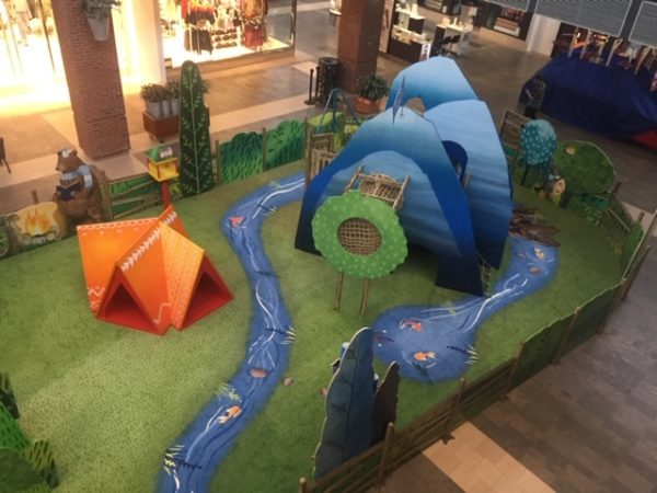 Safe flooring for children installed in shopping mall play area with SafeLandings custom designed carpet resembling a river.