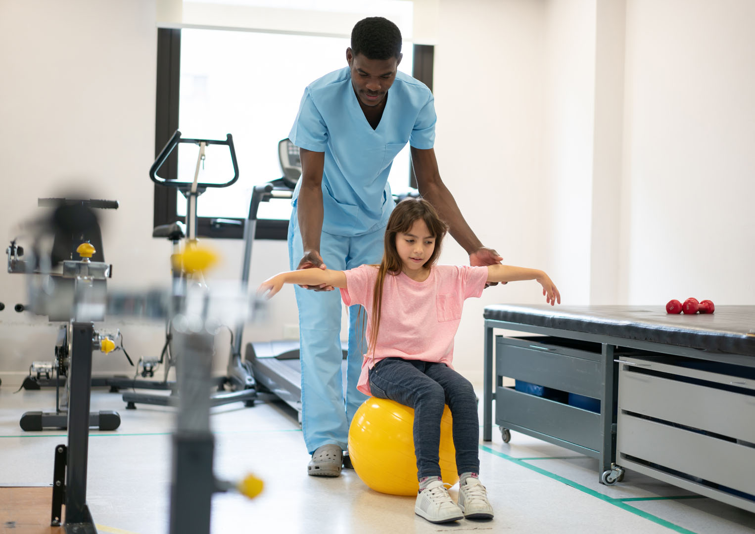Young female child sitting on a yellow balance ball with a male nurse assisting in physical therapy with impact attenuating safe flooring.