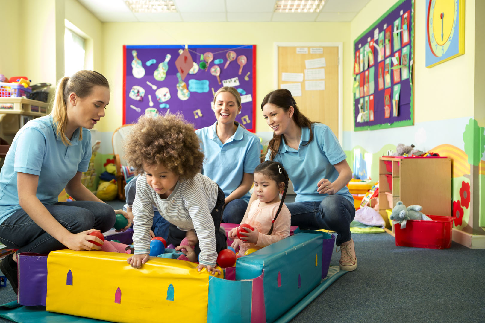 A horizontal image of a group of children in a ball pool playing and laughing, behind them sit three nursery teachers in blue polo shirts supervising and smiling. The nursery is a colourful scene of toys and mess.