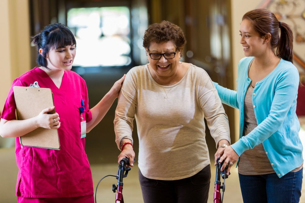 An elderly lady using a walker being assisted by two woman in a physical therapy center.
