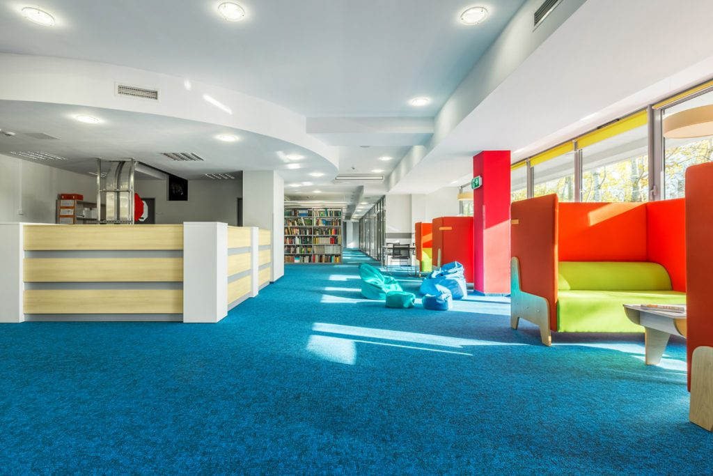 Impact absorbing blue carpeting inside a library story time area.