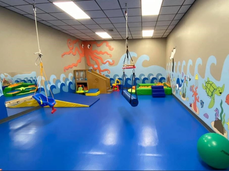 Blue impact attenuating flooring in pediatric therapy center. The walls are painted with ocean animals and waves.